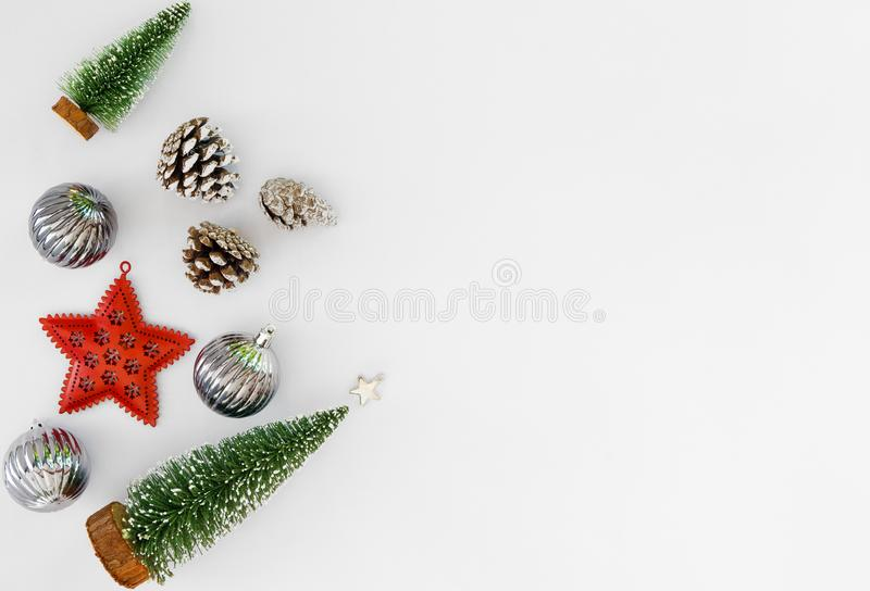 Christmas tree, silver balls, red star and pine cone on white background. stock photos