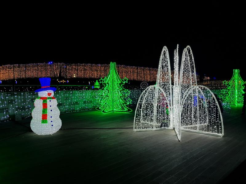 Illuminated Christmas Ornaments with leds at night. Christmas tree, snow man with hat and scarf made from lights in blue red green white color, in park sitting royalty free stock photo