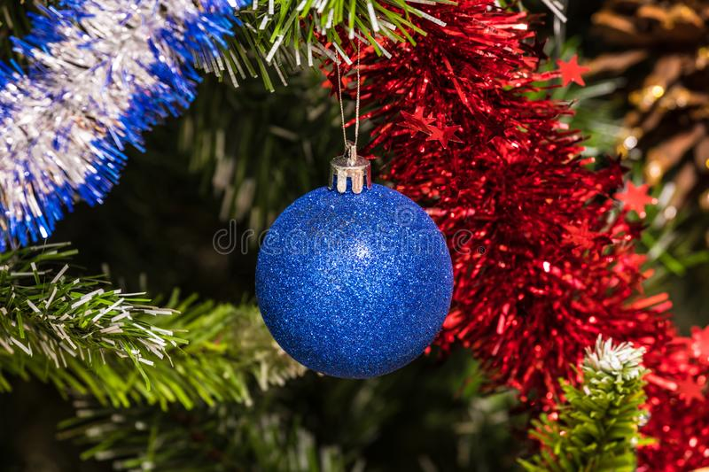 The christmas tree toy, blue ball or sphere on the fluffy artificial pine or fur branch ornament. With red and blue garland stock photos
