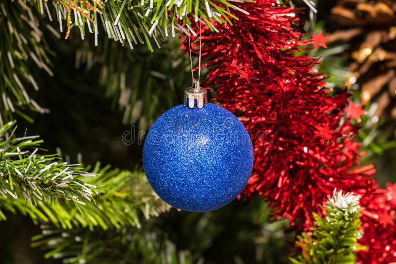 The christmas tree toy, blue ball or sphere on the fluffy artificial pine or fur branch ornament. With red and blue garland stock photo