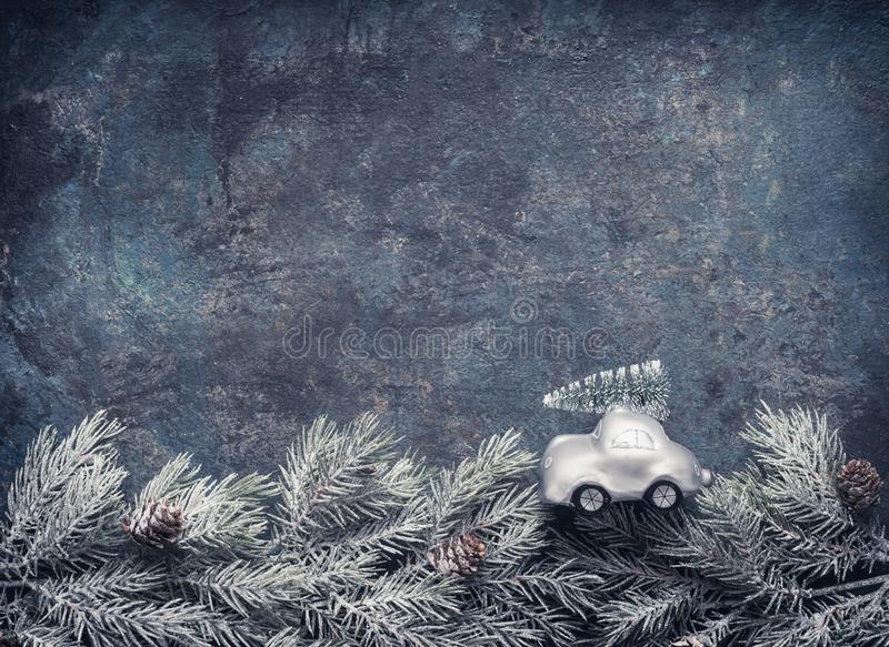Christmas tree on toy car rides on fir branches on dar blue background, Holiday greeting card with copy space royalty free stock photography