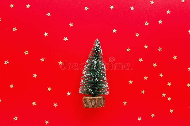 Christmas tree toy and golden confetti on red background. new year concept. Greeting card, winter holidays, xmas celebration 2020 royalty free stock images