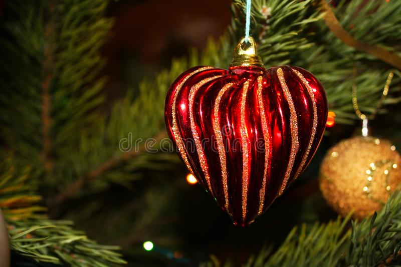 Christmas tree toy with red heart. Christmas tree toy with red sparkle heart and gold ball royalty free stock photos