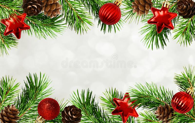 Christmas tree twigs, cones, balls and bokeh background royalty free stock photo