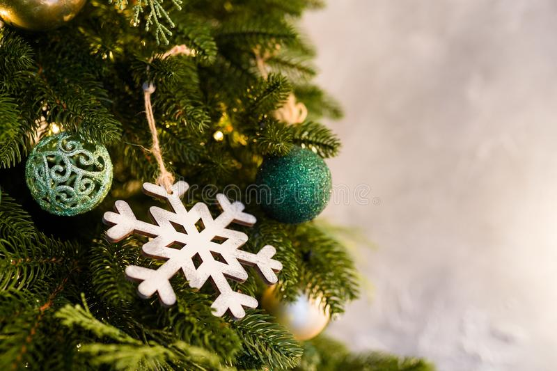 Christmas tree with wood snowflake and colourful balls decoration on gray background, copy space stock image