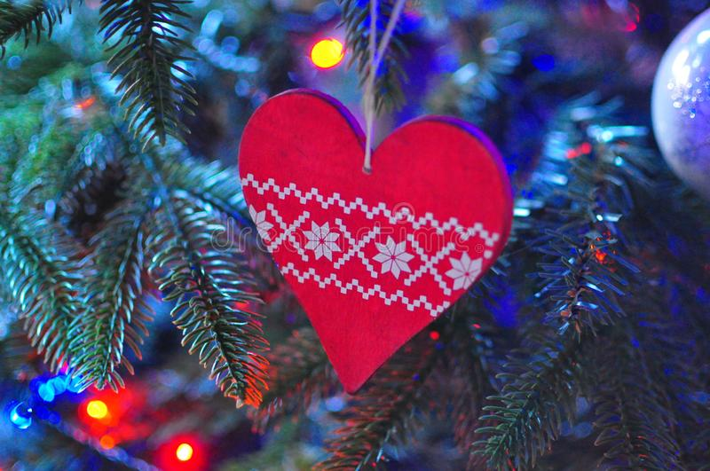 Christmas Tree Wooden Heart Hanging Decoration. A Christmas Wooden Heart decoration, hanging on a Christmas tree with lights royalty free stock photo