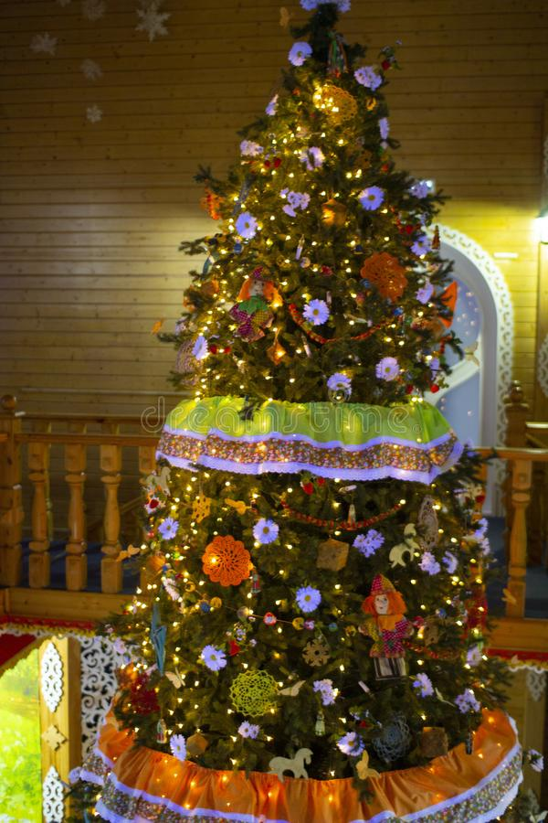 Christmas tree in a wooden house.Christmas tree decorated with lights. Christmas interior background royalty free stock images