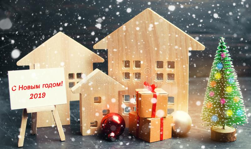 Christmas tree, wooden houses and gifts with `Merry Christmas and Happy New Year 2019` inscription in Russian language. New Year c stock image