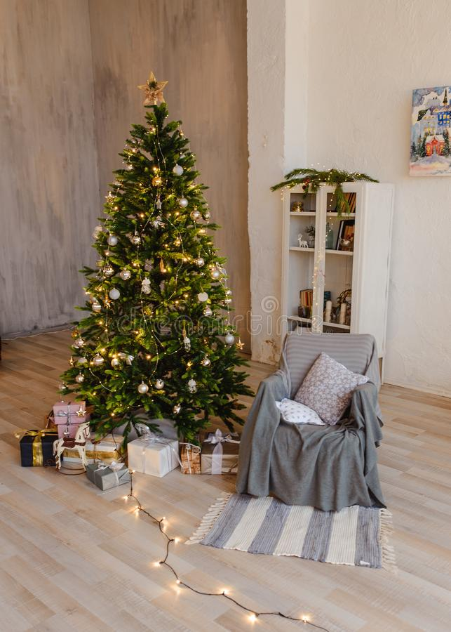 Christmas tree with wooden rustic decorations and presents under it in loft interior. royalty free stock photography