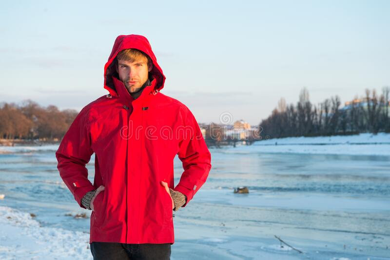 Christmas vacation. human and nature. man walking snowy landscape in sunset. travel and expedition concept. man in red royalty free stock photography