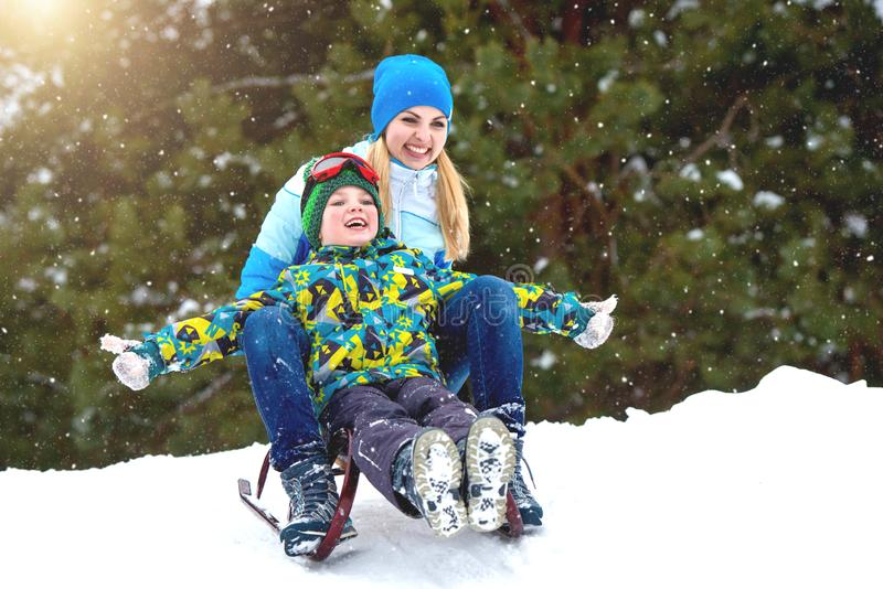 Mother and son ride on sleigh .Child play in snowy forest. Outdoor winter fun for family Christmas vacation. stock photo