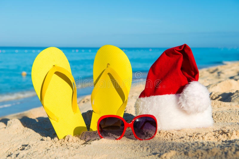 Christmas vacation at sea. Happy New Year holidays. Santa hat, sandals, sunglasses on sandy beach royalty free stock images