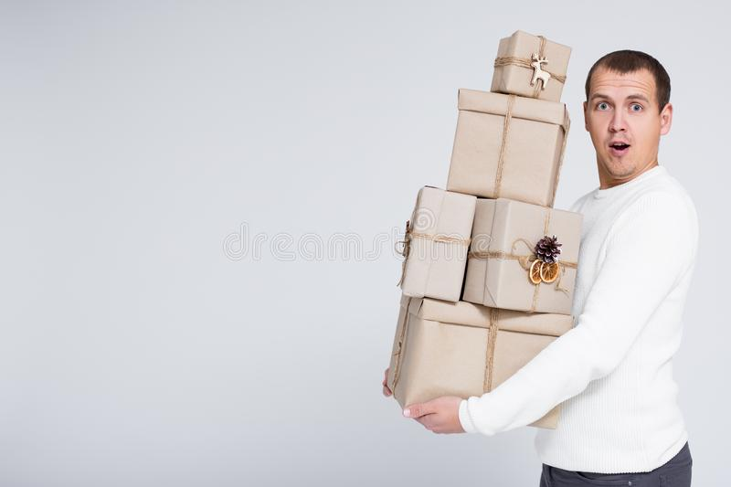 Christmas or Valentine`s day background - handsome man in white warm sweater holding heap of gift boxes over gray background with stock photography