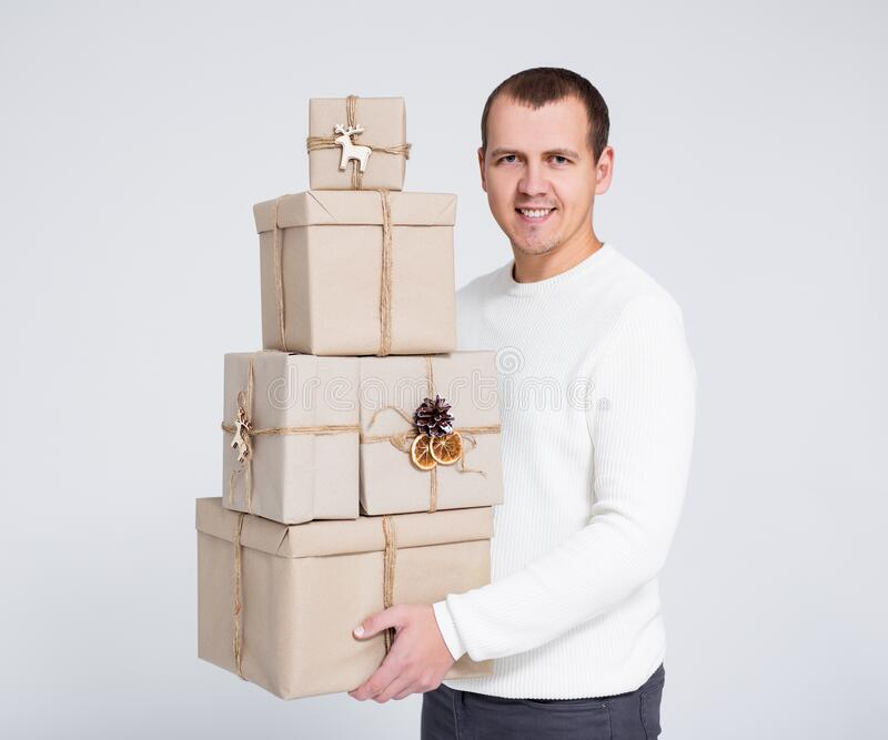 Christmas or Valentine`s day concept - handsome man in white warm sweater holding gift boxes over gray background stock images