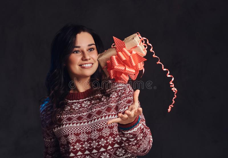 Portrait of a happy brunette girl wearing a warm sweater girl throws up a gift box, isolated on a dark textured stock image