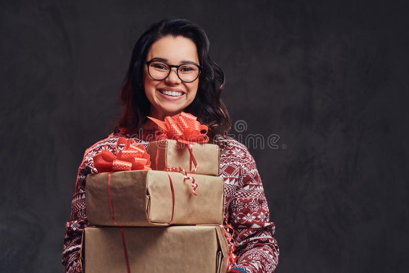 Portrait of a happy brunette girl wearing eyeglasses and warm sweater holding a gifts boxes, isolated on a dark textured stock photography