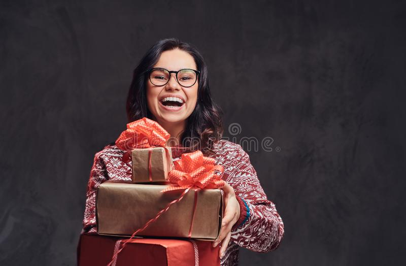 Portrait of a happy brunette girl wearing eyeglasses and warm sweater holding a gifts boxes, isolated on a dark textured stock photo
