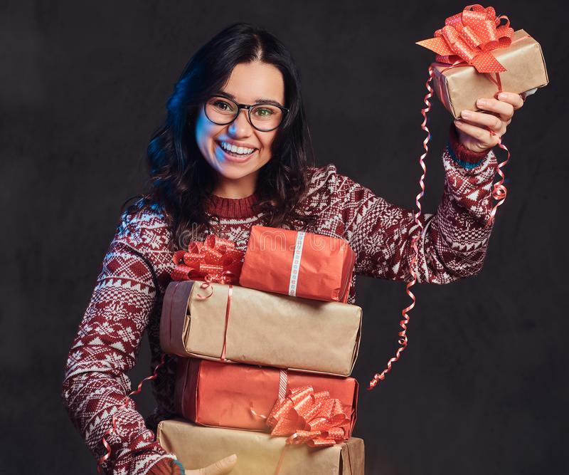 Portrait of a happy brunette girl wearing eyeglasses and warm sweater holding a gifts boxes, isolated on a dark textured royalty free stock photography