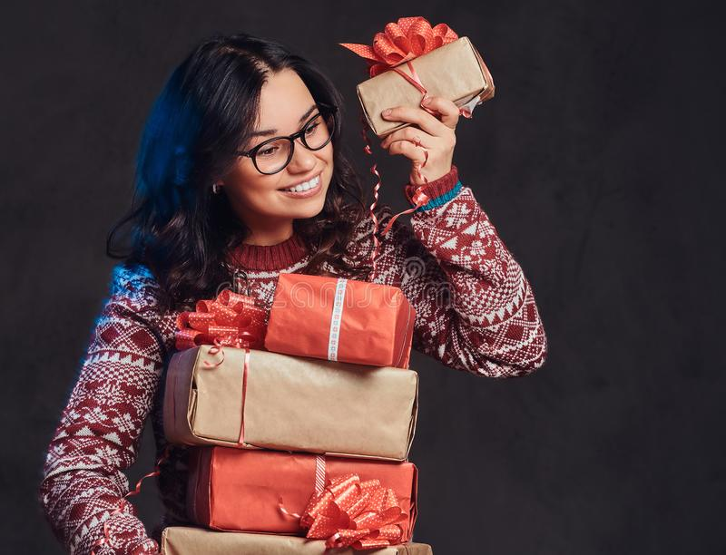 Portrait of a happy brunette girl wearing eyeglasses and warm sweater holding a gifts boxes, isolated on a dark textured royalty free stock image