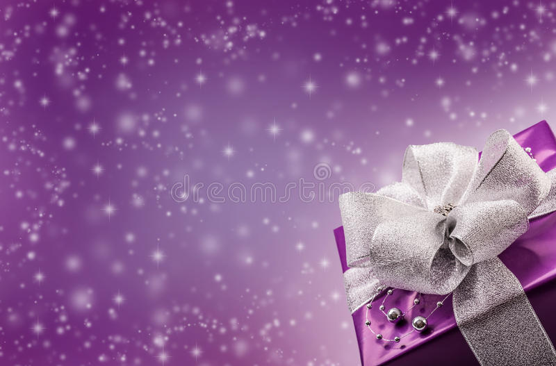 Christmas or Valentine's purple gift with silver ribbon abstract purple background stock images