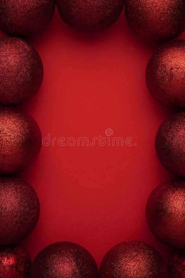 Christmas vertical composition of red ornaments baubles ball. Christmas decorations on red background. Flat lay, top stock photo
