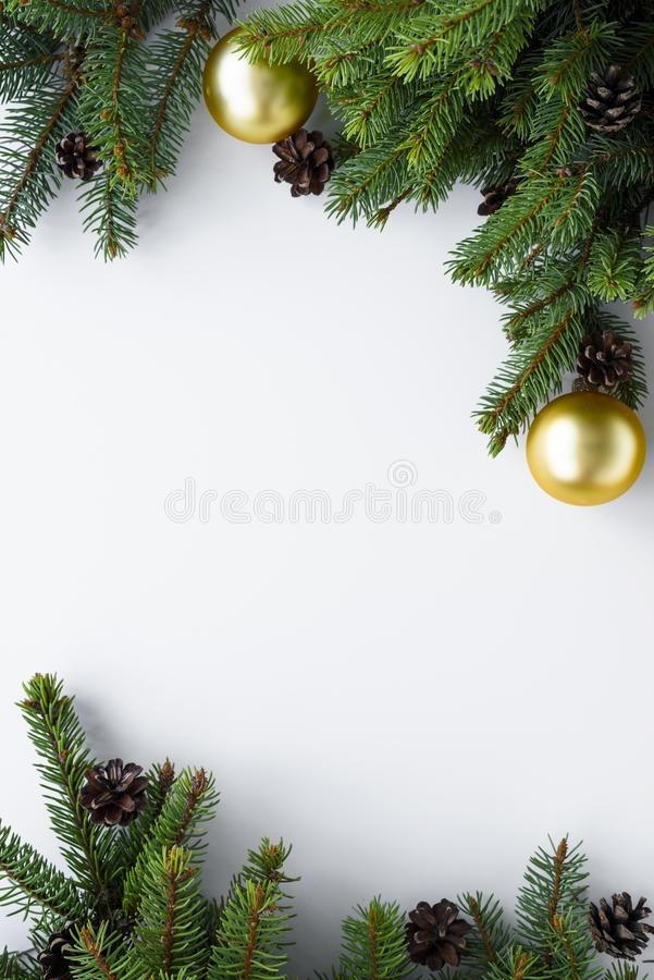 Christmas vertical frame with copy space. Decoration evergreen tree branches, cones and gold baubles. Merry Christmas greeting. Christmas vertical frame with royalty free stock image