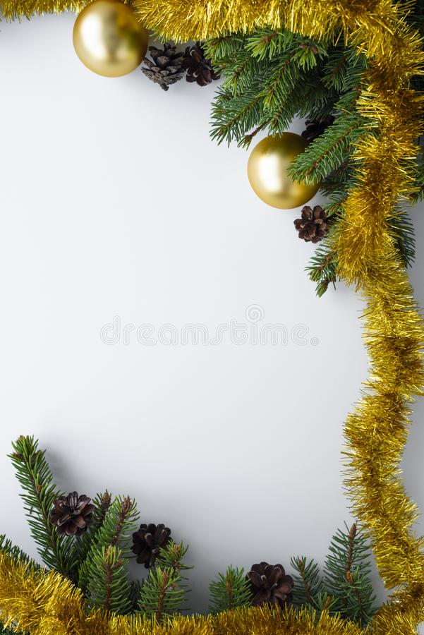 Christmas vertical greeting card with copy space. Ornament decorations such as gold baubles, tinsel, evergreen tree branches and. Christmas vertical greeting royalty free stock photos