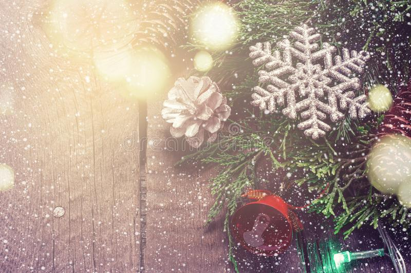 Christmas Vintage card. Coniferous branches and snowflakes on wooden background. Bokeh lights stock images