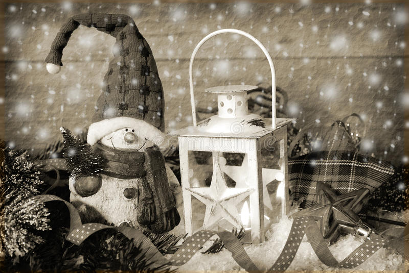 Christmas vintage lantern in snow at wooden background in sepia
