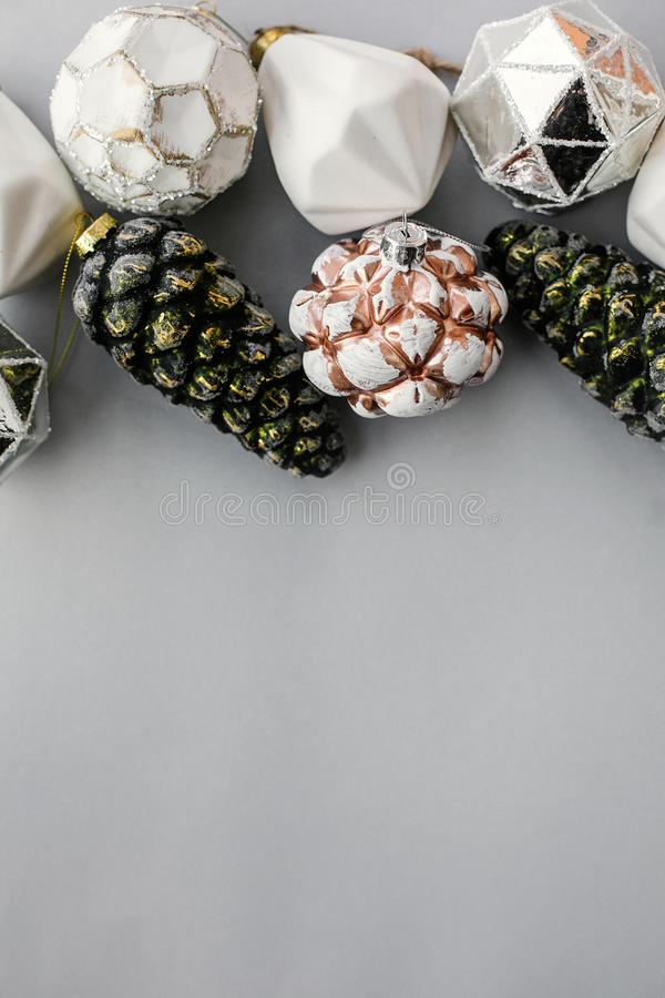 Christmas vintage ornaments on grey paper, flat lay with space for text. Stylish vintage glass baubles and pine cone border, royalty free stock photos