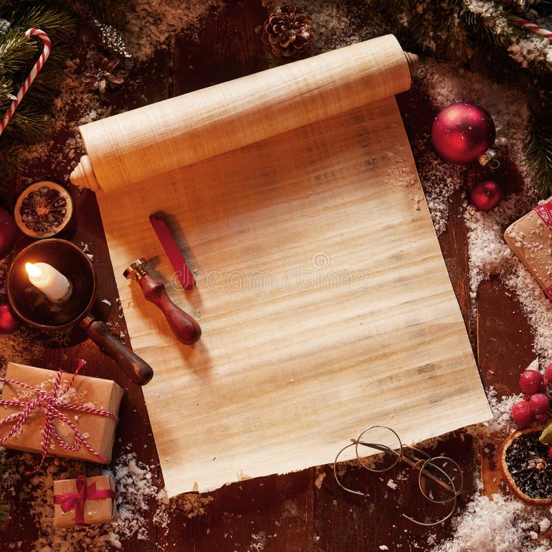 Christmas vintage scroll with spectacles, gifts and decorations surrounded by pine foliage and a burning candle.  royalty free stock images