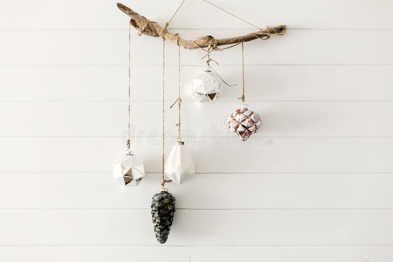 Christmas vintage toys hanging on wooden boho branch on background of white wall in festive modern room. Stylish glass ornaments, royalty free stock image