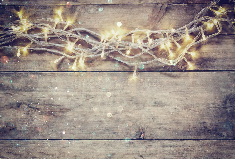 Christmas warm gold garland lights on wooden rustic background. filtered image with glitter overlay. royalty free stock photo