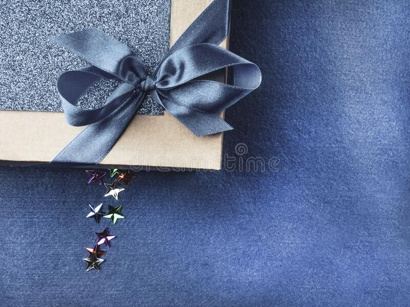 Christmas, weeding, Valentine day gift box or present with bow ribbon on trendy magic blue background. Copy space for greeting. Christmas, weeding, Valentine day royalty free stock images