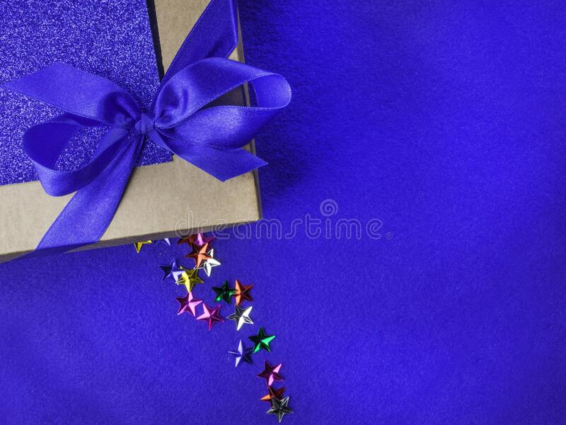 Christmas, weeding, Valentine day gift box or present with bow. Ribbon on trendy magic blue background, colorful stars. Sale concept. Copy space for greeting stock photography