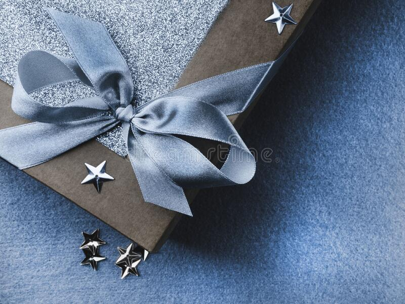 Christmas, weeding, Valentine day gift box or present with bow ribbon on trendy magic blue. Background, colorful stars. Sale concept. Copy space for greeting stock photos