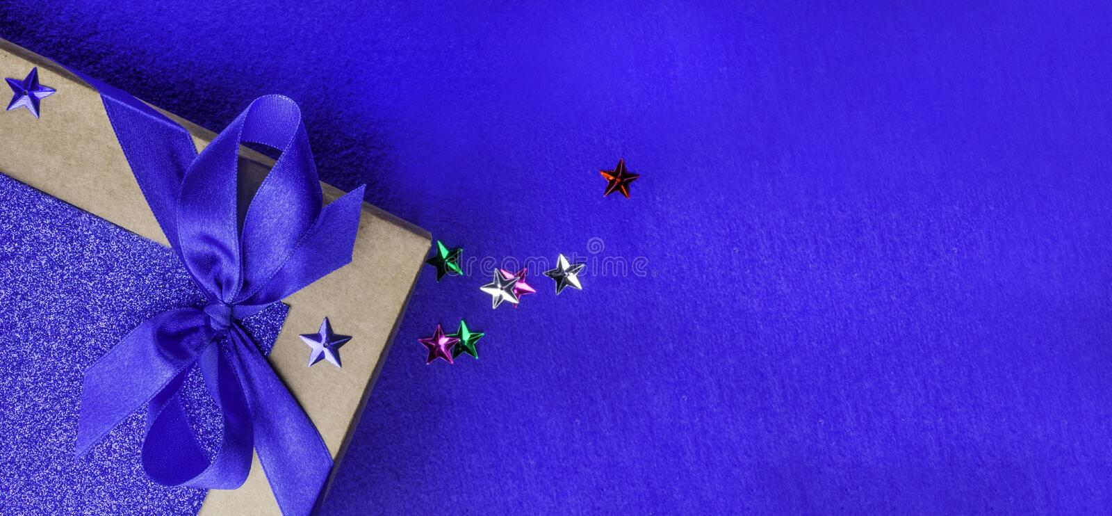 Christmas, weeding, Valentine day gift box or present with bow ribbon on trendy magic blue background. Copy space for greeting. Christmas, weeding, Valentine day royalty free stock photo