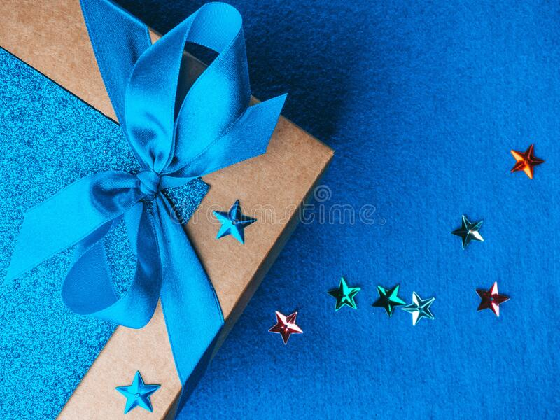 Christmas, weeding, Valentine day gift box or present with bow ribbon on trendy magic blue background. Copy space for greeting. Christmas, weeding, Valentine day royalty free stock photography