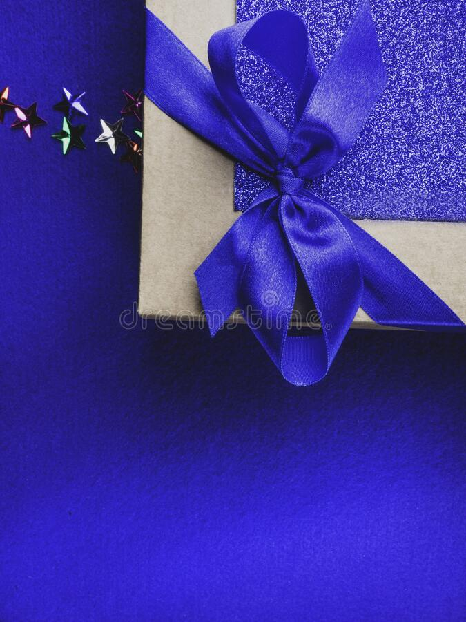 Christmas, weeding, Valentine day gift box or present with bow ribbon on trendy magic blue background. Copy space for greeting. Christmas, weeding, Valentine day stock photos