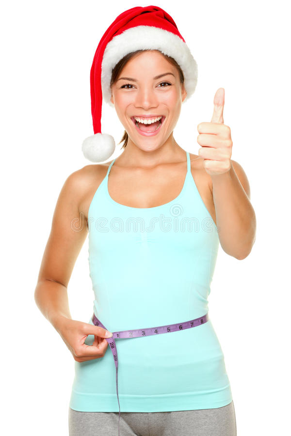 Christmas weight loss fitness concept. Christmas weight loss concept. Fitness woman wearing santa hat measuring waist with measuring tape while showing thumbs up royalty free stock photos
