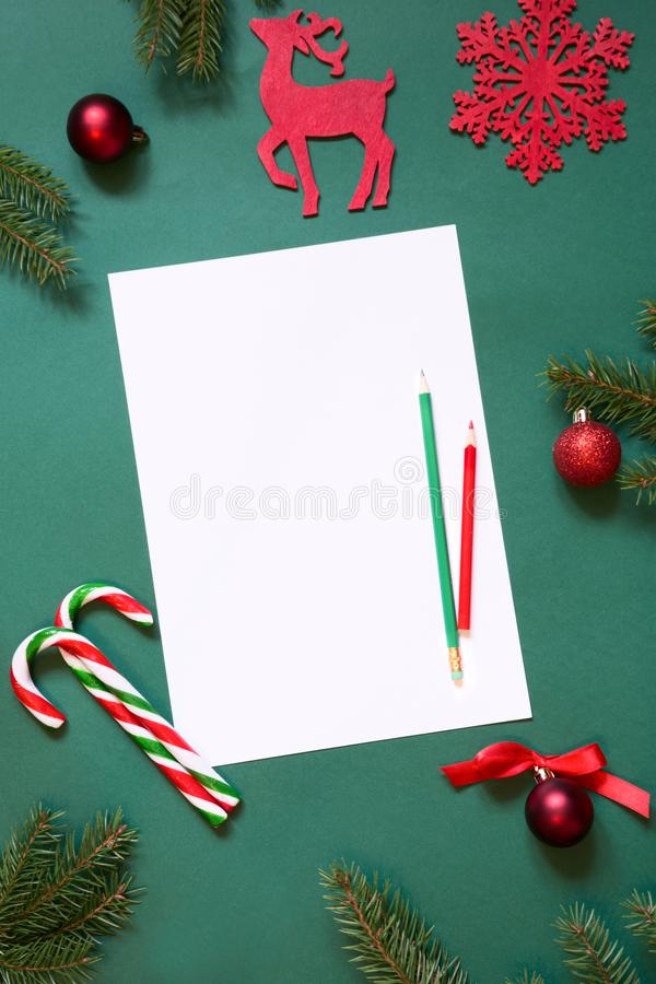 Christmas white blank for letter to Santa or your wish list or advent activities on green background. Top view. Christmas white blank for letter to Santa or stock images