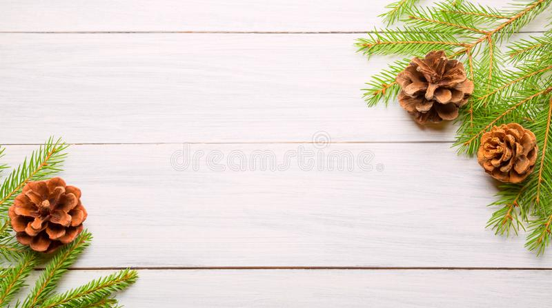 Christmas white wooden background with fir tree branches and cones. Top view with copy space for your text. Banner format stock photo