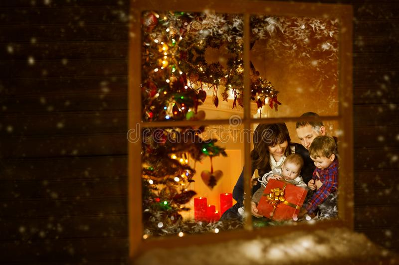 Christmas Window, Family Celebrating Xmas Holiday inside Home. Mother Father Child Baby stock images