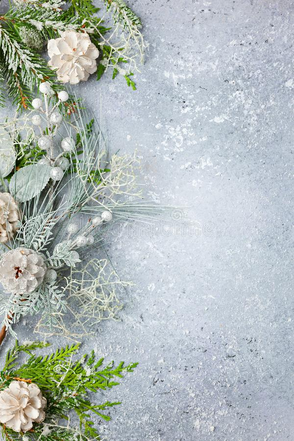 Christmas or winter background with a border of green and frosted evergreen branches and pine cones on a grey vintage board. Flat. Lay, winter concept with copy royalty free stock photography