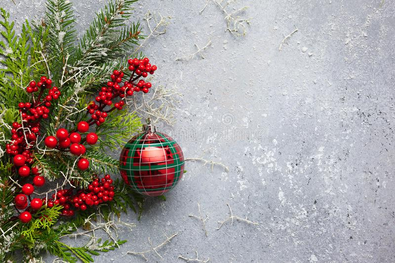 Christmas or winter background with a border of green and frosted evergreen branches, red berries and Christmas bauble on a grey. Vintage board. Flat lay royalty free stock photo