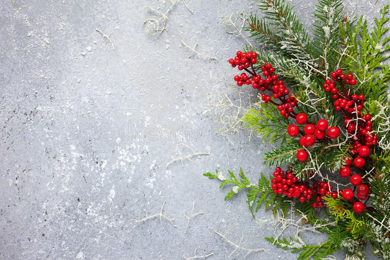 Christmas or winter background with a border of green and frosted evergreen branches and red berries on a grey vintage board. Flat. Lay stock images