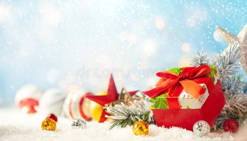 Christmas winter background with gift box, Christmas baubles and fir tree branches on snow. Christmas winter background with Christmas baubles and fir tree royalty free stock photography