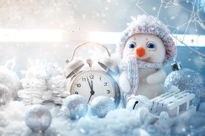 Christmas winter a background, the small snowman stands with a clock. Happy New Year. Merry Christmas. royalty free stock photos