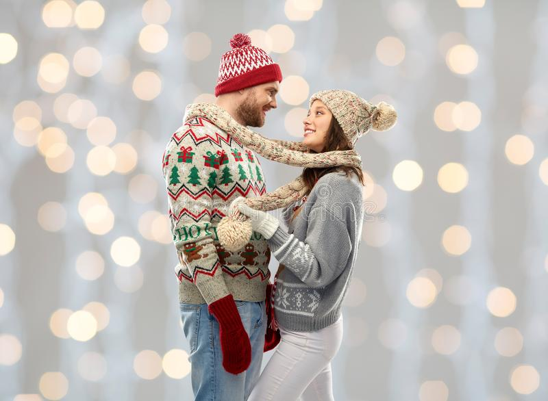 Happy couple at christmas ugly sweater party. Christmas, winter clothes and holidays concept - portrait of happy couple in ug sweaters, knitted mittens and hats royalty free stock photo