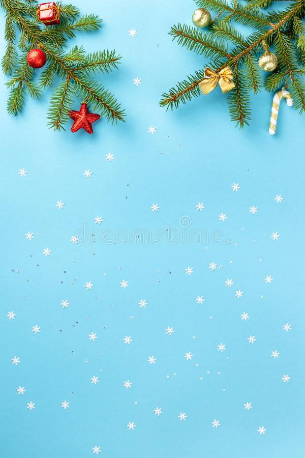 Christmas and winter composition. Frame made of fir branch, golden and red toys and white snowflakes with tinsel on pastel blue stock photos
